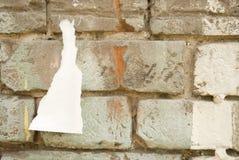 Backsteinmauer mit einem Stück eines Plakats Stockbild