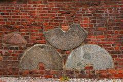 Backsteinmauer mit eingebetteten Mühlsteinen Lizenzfreie Stockfotos