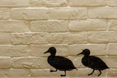 Backsteinmauer mit gehenden Enten des Schattenbildes Lizenzfreie Stockbilder