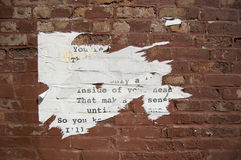 Backsteinmauer mit heftigem Papier Stockbild