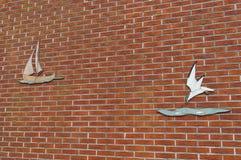 Backsteinmauer mit Kunstdekoration (Segelboot und Seemöwe) Lizenzfreies Stockbild