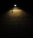 Backsteinmauer mit Leuchte Stockbild