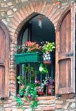 Backsteinmauer mit roten Blumen auf Fenster Lizenzfreie Stockfotos