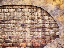 Backsteinmauer mit schädigendem Gips, alte Hintergrundbeschaffenheit Stockfoto