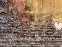 Backsteinmauer mit schädigendem Gips, alte Hintergrundbeschaffenheit Lizenzfreie Stockfotografie