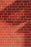 Backsteinmauer mit Schatten auf ihm Lizenzfreie Stockfotos