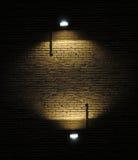Backsteinmauer mit Scheinwerfern Stockbild