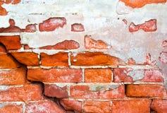 Backsteinmauer mit Sprüngen und einem alten Gips als Hintergrund Lizenzfreies Stockbild