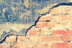 Backsteinmauer mit Sprüngen und einem alten Gips als Hintergrund Stockfotografie