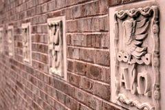 Backsteinmauer mit SteinCarvings Stockfotografie