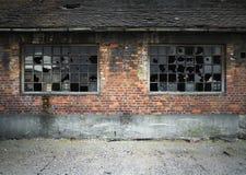 Backsteinmauer mit zerbrochenen Fensterscheiben Stockbild