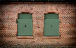 Backsteinmauer und alte Stahlblendenverschlüsse geschlossen Stockfotos