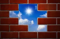 Backsteinmauer und blauer Himmel mit Wolken. Stockfotos