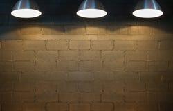 Backsteinmauer und drei Scheinwerfer stockbilder