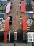 Backsteinmauer und geöffnete Fenster Stockfotos