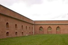 Backsteinmauer und grünes Gras Stockfotos