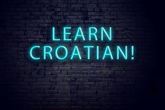 Backsteinmauer und Leuchtreklame mit Aufschrift Konzept des Lernens von Kroatisch stockfotos