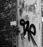 Backsteinmauer und Tür mit Graffiti Stockfotografie