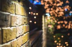 Backsteinmauer-Weihnachtshintergrund mit dem Lichtglühen lizenzfreie stockfotografie