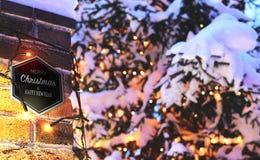 Backsteinmauer-Weihnachtshintergrund mit dem Lichtglühen und Schnee, Karte Lizenzfreie Stockfotos
