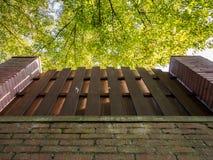 Backsteinmauer, Zaun und Bäume lizenzfreies stockfoto