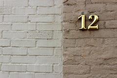 Backsteinmauer in zwei Farben der Sonnenbräune und des Brauns mit einem Gold 12 anscheinend Stockfotografie