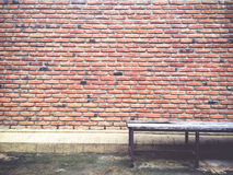 Backsteinmauerbeschaffenheit und -muster mit altem Stuhl Stockbild