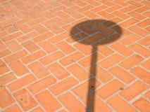 Backsteinmauerhintergrund gemasert mit Schatten des Verkehrszeichens Stockfotos