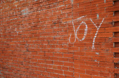 Backsteinmauerhintergrund mit der Wort Freude auf der Wand Stockfoto
