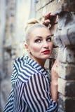 Backsteinmauerhintergrund mit einem Mädchen Stockfotografie