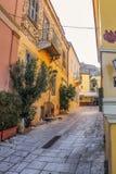 Backstreet de Atenas que mira para arriba la pared de la acrópolis con los cafés al aire libre en la distancia foto de archivo libre de regalías