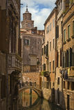 Backstreet in Venice, Italy. A quiet canal reflects the surrounding buildings Royalty Free Stock Image