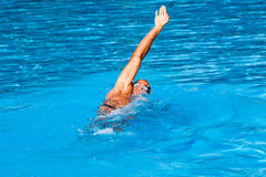 Backstroke swim style. Young man swim backstroke style in outdoor swimming pool, sunny summer day Royalty Free Stock Images