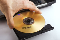 Backup. A hand and a dvd stock photos