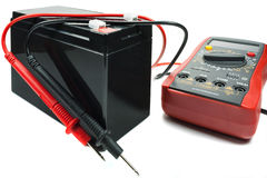 Backup battery with a multimeter and probes on a white background Stock Images