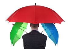 Backup insurance plan. Confident businessman with three umbrellas concept for more than adequate ample insurance cover or failsafe backup plan Stock Photography
