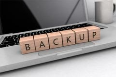 Backup text concept. Lettered wooden cubes on notebook computer- 3D render illustration Royalty Free Stock Photos