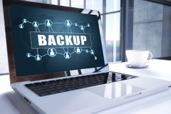 Backup. Text on modern laptop screen in office environment. 3D render illustration business text concept Royalty Free Stock Photography