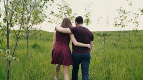 Backview ενός αγαπώντας ζεύγους που περπατά σε έναν κήπο Αγκαλιάζοντας τους εραστές απολαύστε το αργό MO φύσης, steadicam πυροβολ φιλμ μικρού μήκους