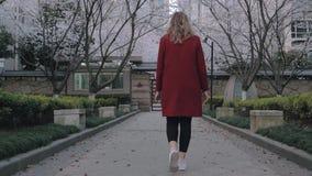 Backview του ελκυστικού ξανθού κοριτσιού σε ένα κόκκινο παλτό που περπατά την αλέα sakura, που απολαμβάνει τη μυρωδιά των ανθίζον φιλμ μικρού μήκους