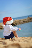 Backview του παιδιού στη συνεδρίαση καπέλων Santa στην ακτή Στοκ Εικόνα