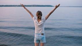 BackView молодой дамы повышения вручает праздновать славное лето выравниваясь около озера сток-видео