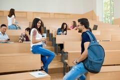 Backview студентов связывая в университете Стоковое Изображение RF