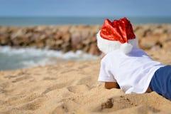孩子Backview说谎在沙子岸的圣诞老人帽子的 免版税库存照片