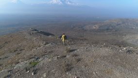 Aerial view: one man walking on the fog mountain. Backview aero shot: guy motion on the way to the peak and looking at cloudy skyline. Cliff ridge in autumn sun stock footage