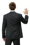 Backview av den vinkande handen för affärsman royaltyfria foton