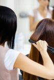 Backview av frisören som gör hårstil för kvinna royaltyfri foto