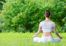 Backview av kvinnan, i att göra en gest för zen för lotusblommaposition royaltyfri bild