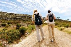 Backview av två unga kvinnor som fotvandrar i natur royaltyfri bild