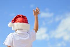 Backview av ungen i röd jultomtenhatt med den lyftta handen Arkivfoto